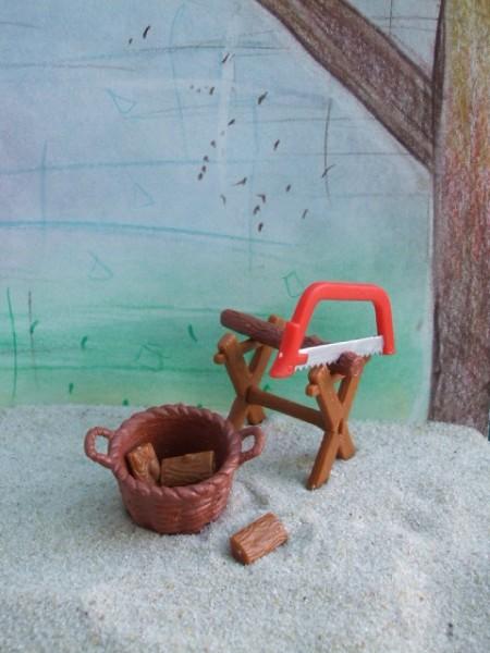 Sägebock mit Säge & Korb mit Holzscheiten
